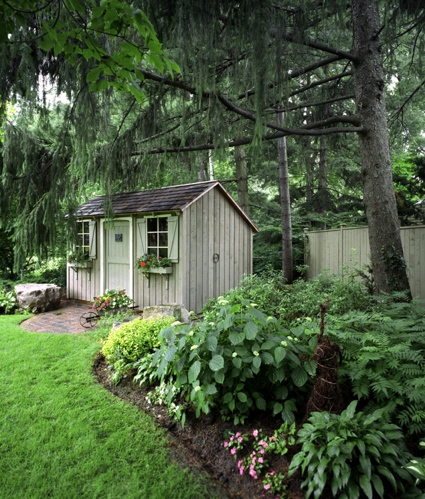This beautiful yard has fresh and bright green grass, and beautiful flowers and brush surrounding the base of massive trees.
