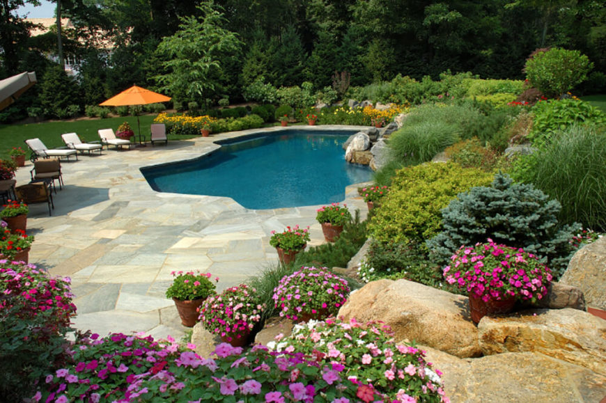 The patio is made with a unique stone pattern of different shades and sizes. The crystal clear pool is cut into the patio with another unique shape.