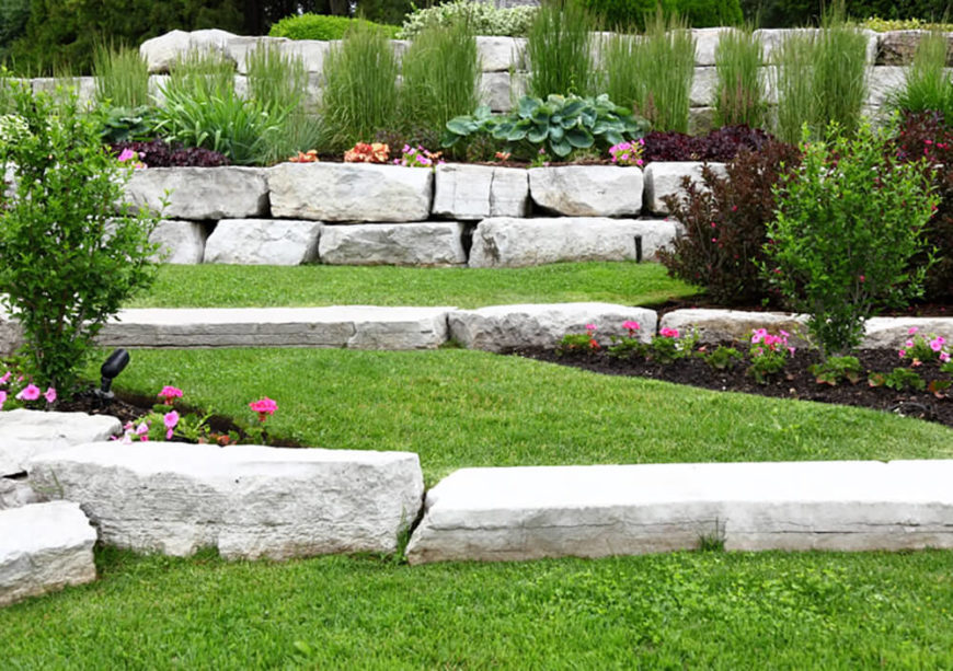 The large stone slabs used to create a tiered landscape in this yard make a statement all on their own. The chosen plants only add to this bold garden.