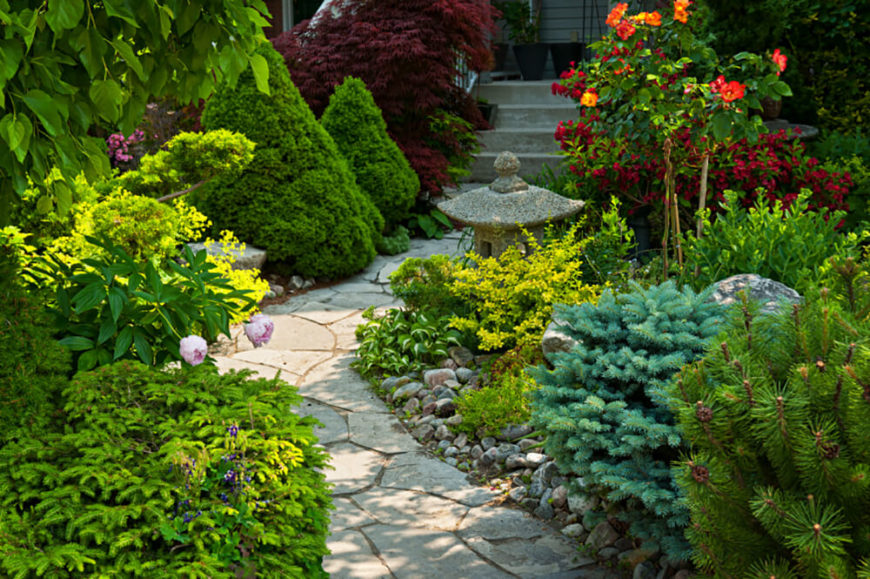 This calming garden features small shrubbery and a Japanese lantern along the pieced-together pathway. The bright red flowers and foliage in the background balance out the amount of greenery in the foreground.