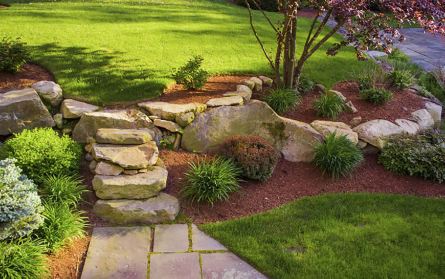 This beautiful sand-colored walkway and border stand out well against the green and red of this garden. The mulch ties into the greenery with touches of red in the bushes and the red maple.