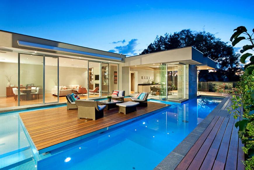 "Moving around the side of the home, we see the ""floating"" patio section, completely detached from the home by a slim channel of water. A set of relaxing rattan furniture makes this a prime social space."