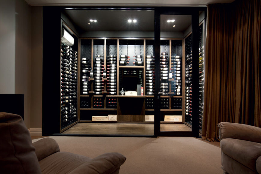 Here we have the bespoke wine cellar, flush with dark wood and entered through an all glass wall and door. A large curtain divides the room and obscures the wine cellar when not in use.