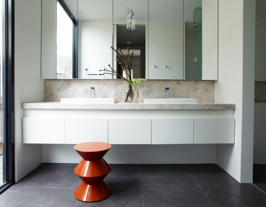 The bathroom features a floating dual vanity with marble countertop and backsplash, bracketed between sleek white drawers and frameless mirrors. A singular conical stool stands over large format grey tile flooring.