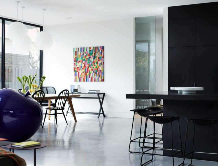 Across the wide expanse of white flooring, we see the dining room area, with natural wood table and black chairs beneath a trio of spherical lights. A fractal rainbow painting hangs on the white wall, adding a small but powerful bloom of color in the room.