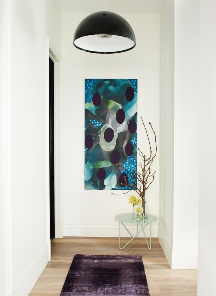 The hallway to the private areas of the home features light hardwood flooring, for a softer pairing with the white walls. Furthering the overall theme, a single colorful painting and purple rug puncture the neutral palette.