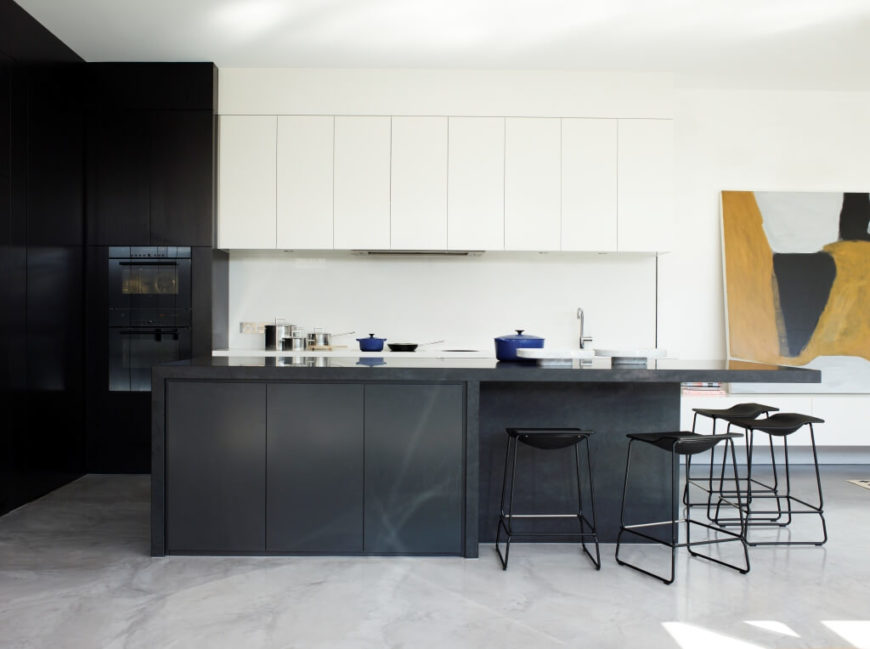 The kitchen centers on a large charcoal toned island, its contrast emphasized by both pristine white and dark wood cabinetry. The island houses an extended countertop, with space for several modern black bar stools.