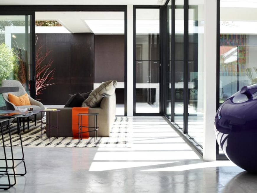 Viewed from the dining area, we see the minimalist living room setup wrapped in glass and, at left, rich dark wood wall panels. Sunlight fills this entire open space, highlighting the spare bursts of color.