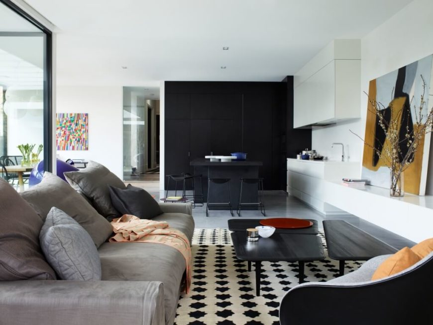 The living room is defined by a black and white area rug, with contemporary plush sofa and club chair facing over a novel rectangular dark wood coffee table, comprised of three complementary pieces.