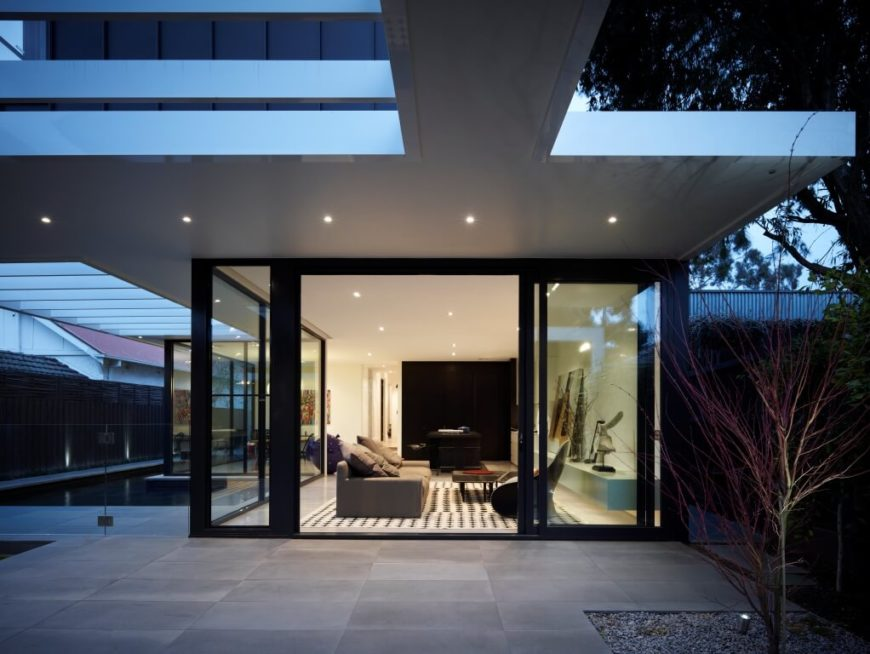 Viewed over the patio at night, we see the line between indoors and out blurred, with an oversized sliding glass door and recessed lighting continuing to the edges of the eaves.