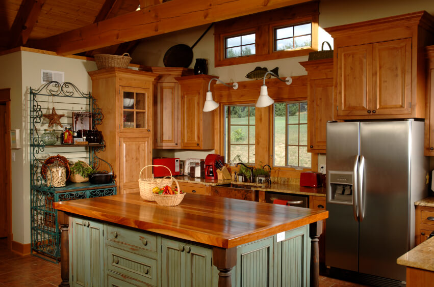 Despite its more rare appearance, hardwood countertops are one of the best options available for both style and utility, when it comes to designing a kitchen island. This example features a rustic-styled base with old fashioned cabinetry painted hazy green, contrasting with the sleek, rich stained wood countertop.