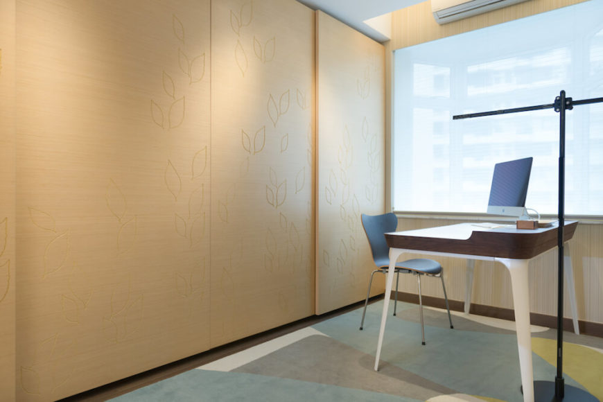 The office space has a whimsical rug full of neutral hues and shapes for a splash of color. The wooden wall has very delicate leaves drawn into it and a hidden doorway.