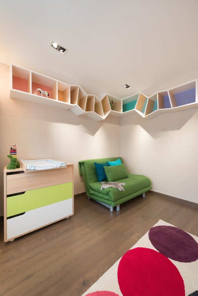 The children's room is incredibly playful and fun. Strange colorful shapes create a shelving unit across the top of the wall, and large colored dots speckle the rug on the floor.