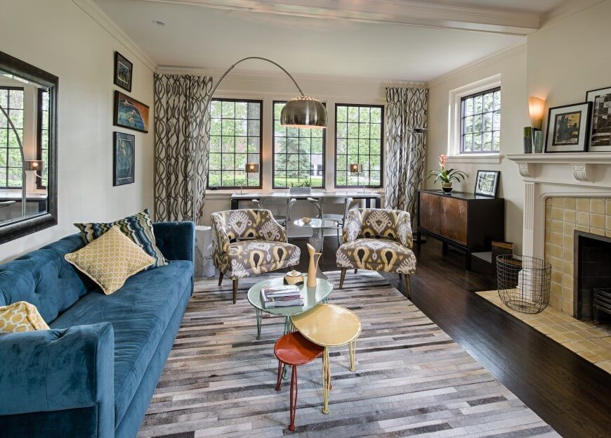 This contemporary living room features a stone tile fireplace and layered patterns. The dark wood flooring adds a solid undertone to the space.