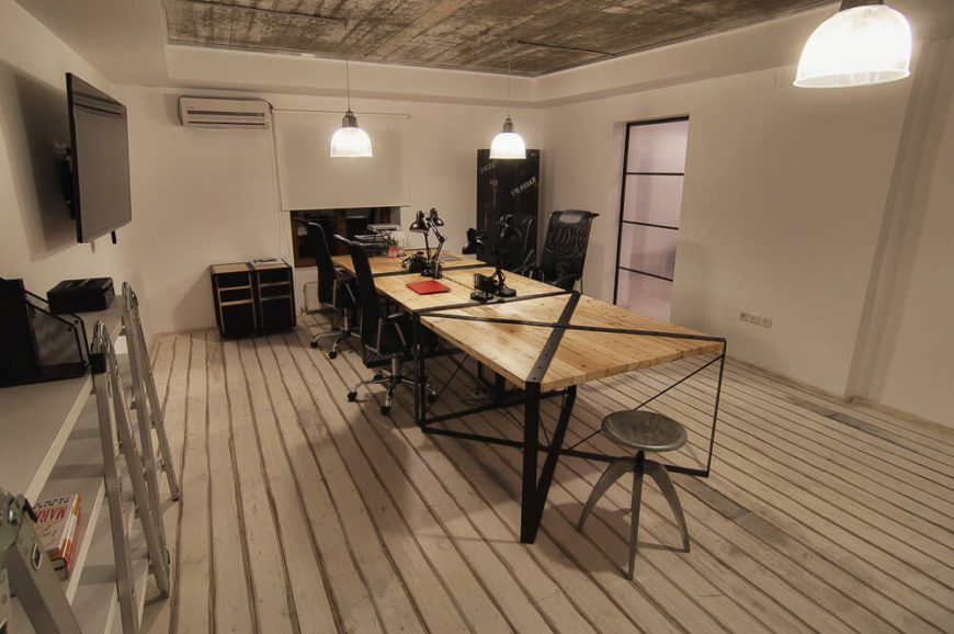 One of the conference rooms follows the industrial and rustic look of the main office, with plenty of lighting for an efficient work space.