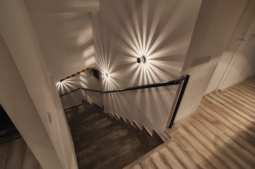 The stairwell is made of a rich chocolate hardwood and leads up to the main space. Lights lining the wall create a unique star-burst pattern of light.