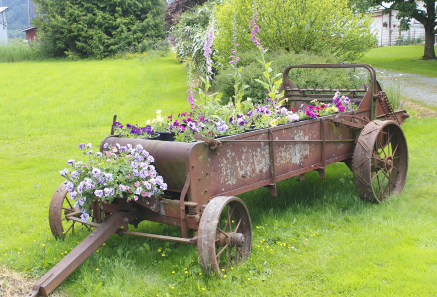 This one utilizes old farming equipment for a country chic look. For a smaller yard, an old wagon or wheelbarrow could achieve the same look.