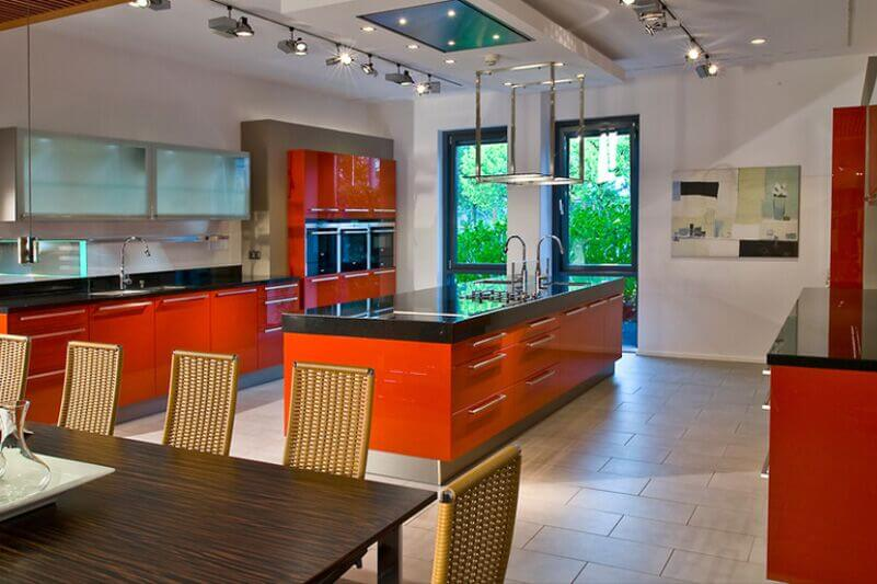 This ultra-modern kitchen bursts with color and contrast, with bright red cabinetry and dark countertops. The large island features dual sinks and a built-in stove top.