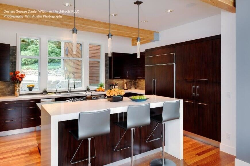 Another high contrast kitchen, this example features dark natural wood cabinetry contrasting with white countertops and lighter hardwood flooring. The two-level island features raised dining space and a built-in stove.