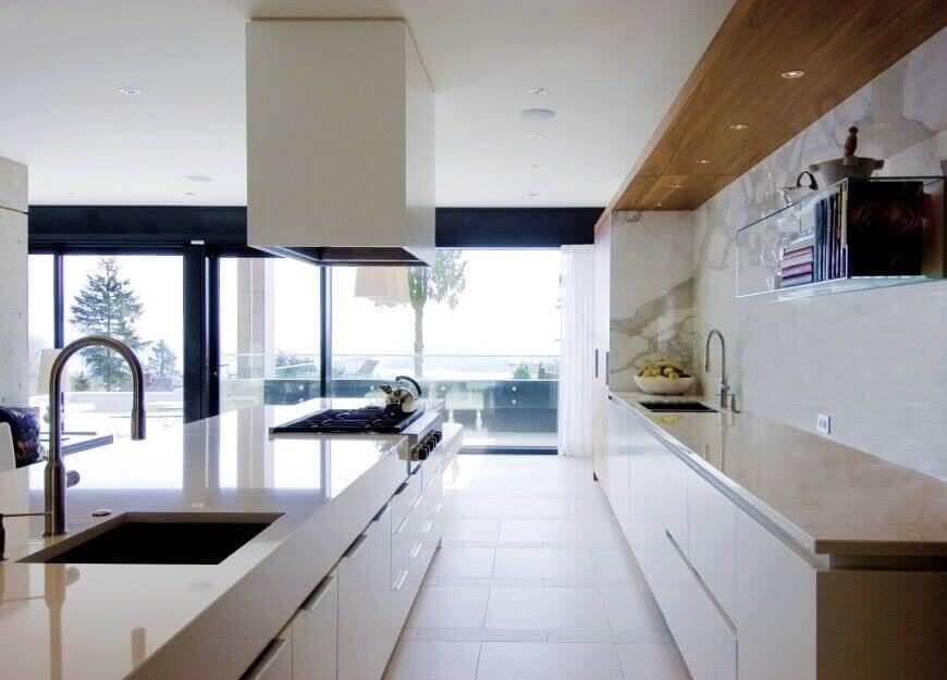 This sleekly modern kitchen appears brightly lit via wraparound glazing, with light hued tile flooring, walls, and countertops. The lengthy minimalist island features a full secondary sink as well as a large stainless steel gas top range.