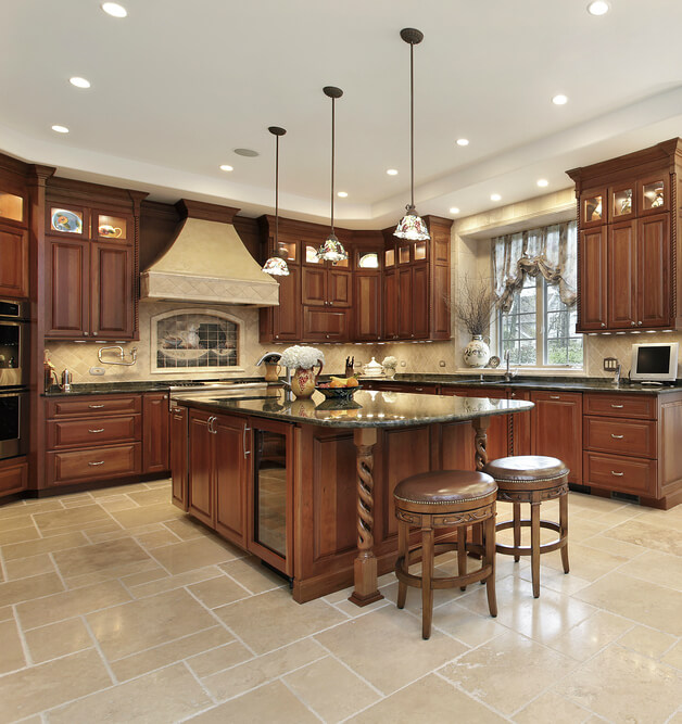 In a richly appointed, traditionally styled dark wood kitchen, a matching island commands attention at center. Featuring a broad dark marble countertop and built-in sink, the island also houses cabinetry and a glass door wine rack. The end of the countertop extends to offer dining space for a pair of leather upholstered, nailhead trimmed bar stools.