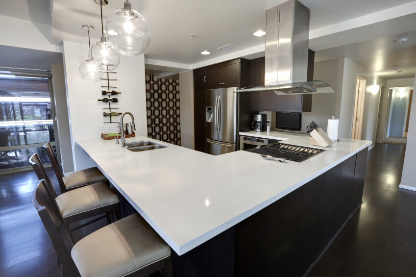 This sleekly contemporary kitchen sports dark hardwood flooring and cabinetry tones to match, with a massive L-shaped island defining the entire space. Glossy white countertops add a wealth of contrast and brightness, housing both a sink and large gas range.