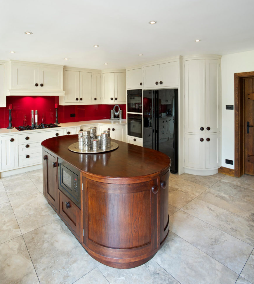 Curved cabinetry is the defining feature of this modern kitchen, reflected on the abundant white cabinetry and the natural wood island alike. With large format grey tile flooring and a burst of red, courtesy of the backsplash, the kitchen is flush with textural detail. The island itself is a unique oval shape, with built-in microwave and plentiful storage.