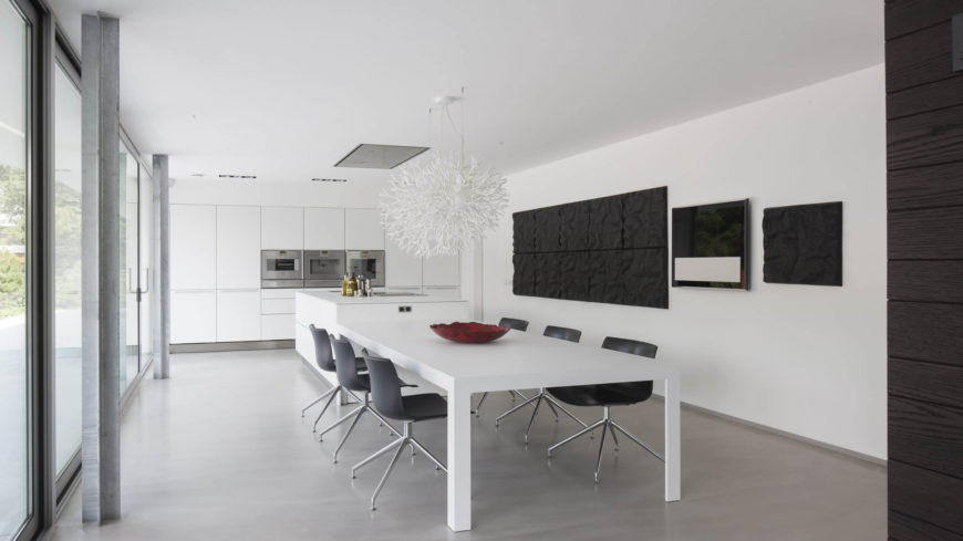 The dining room and kitchen are in an open floor plan together. The black and white colors of the room, along with the abstract center piece above the table, make this space a contemporary primarypiece.