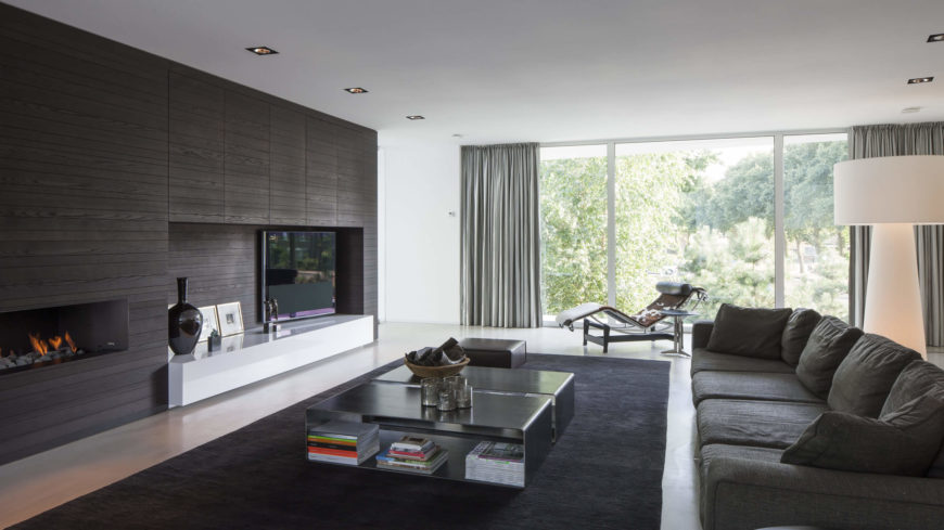 The living room features dark furniture and black accents to contrast the white of the floor and walls. A large window brings a wealth of light into this space, giving it a tranquil and welcoming radiance.