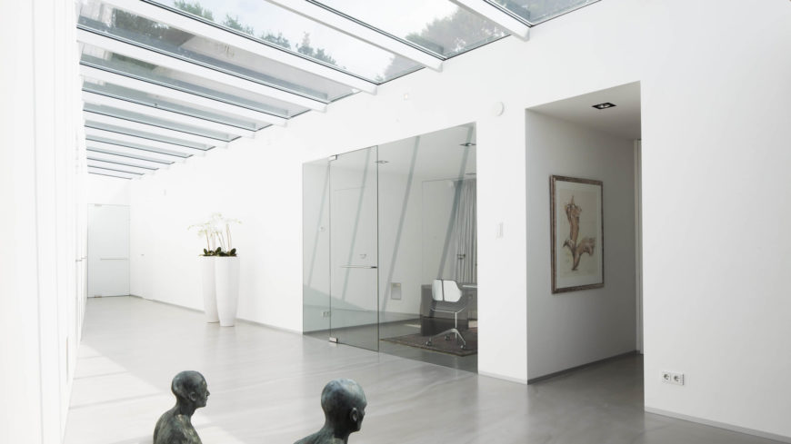 This brilliant white hallway is illuminated by large rectangular skylights. The corridor starts off wide, and narrows as it reaches the door at the end of the hallway, giving it a unique shape and feeling.