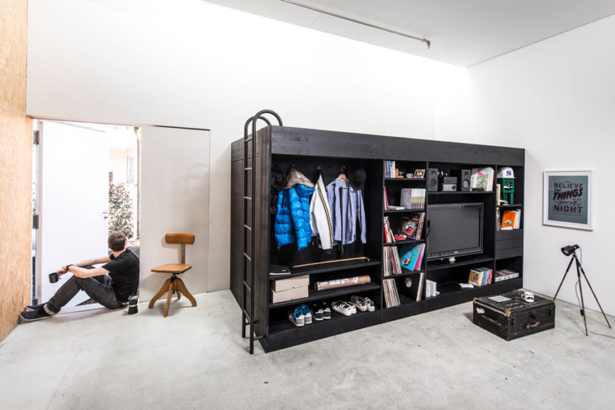 The living cube has an entertainment center and a coat-hanger for an all-in-one piece. A bed is accessible on the top from a ladder.