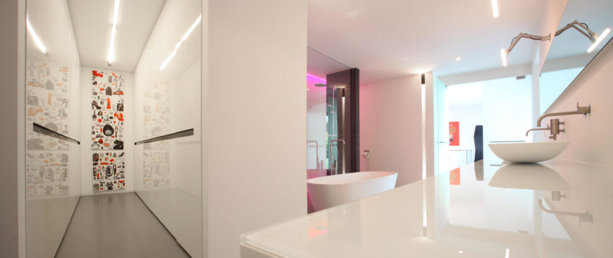 Here we can see another angle of the bathroom that reveals the glass countertop and vessel sinks. Take note of the change of color in the neon light from purple to pink. The neon lights change color for a playful addition to the bathroom.