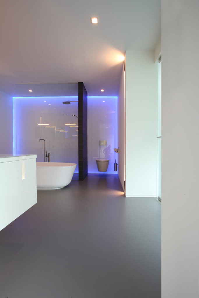 The glossy white bathroom has a large glass shower and sleek pedestal tub for a futuristic style. A hidden neon light rounds the perimeter of the far wall of the bathroom for a splash of color.