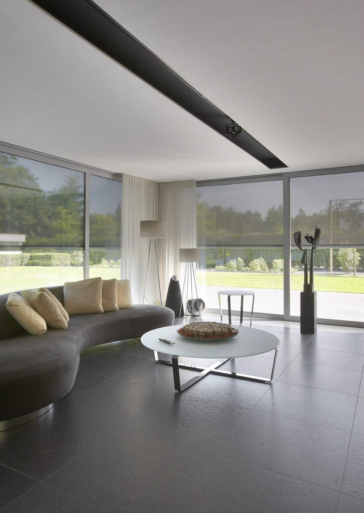 Here on the ground level, the open plan design connects this minimalist living room to the kitchen and dining areas. Full height glazing all around can be cleverly transformed into an opaque wall by the grey pull-down shades, granting privacy to a space that includes a unique curved modern sofa and smoked glass coffee table.