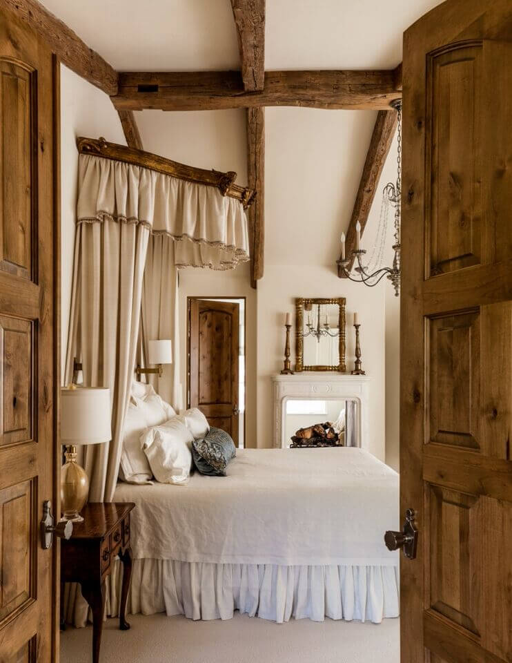 Rustic double doors provide entrance to this lovely traditional primary bedroom with a touch of rustic charm. A passthrough fireplace is shared with the primary bathroom beyond. A half-canopy rises above the headboard, adding further elegance with thick cream drapes.