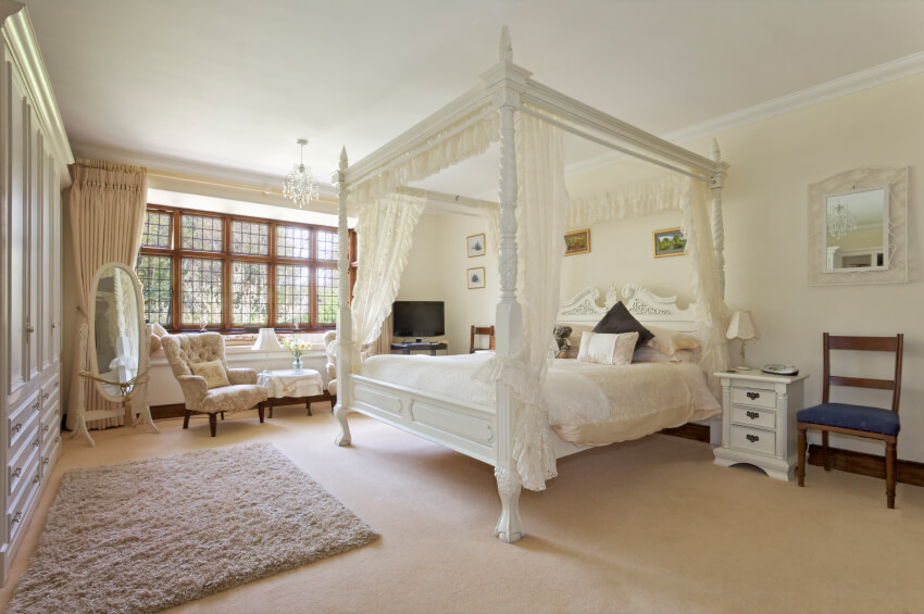 The focal point of this traditional-contemporary primary bedroom is the ornately carved canopy bed with lace drapes and valances. All the storage ever needed is contained within a wall of built-ins.