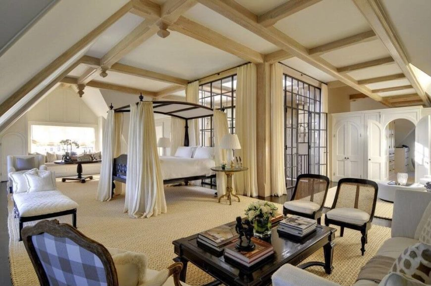 The sheer enormity of this primary suite is awe-inspiring. Exposed beams throughout add an architectural detail that is difficult to ignore. A large glass enclosure in the center of the room leads to the stairs.