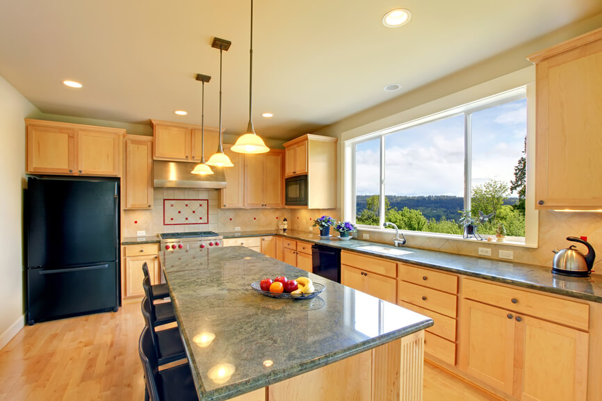 This is a bright and classic kitchen in light wood and matte black appliances. A light tinge of green in the granite countertops brightens up the space further.