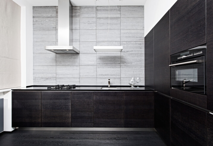 This L-shaped ultra-modern kitchen features textured dark wood minimalist cabinetry with inset black appliances. The vent hood is in stainless steel, which contrasts with the cabinetry and complements the light gray backsplash.