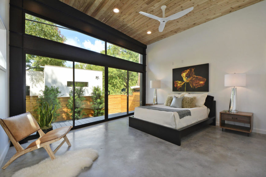 Primary bedroom features a vaulted wooden shiplap ceiling with a mounted white fan. It has a light wooden chair accented with a faux fur rug over concrete flooring.