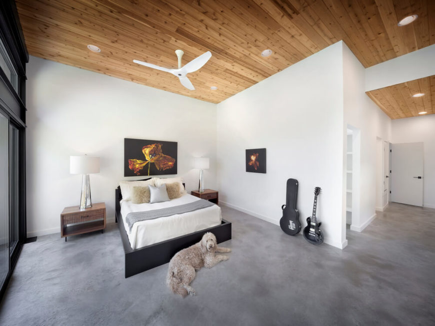 At the far end of the private wing of the home, we see the primary bedroom suite, with rich tongue-and-groove wood ceiling adding a natural warmth to the space. The open-plan area leaves plenty of space for movement.