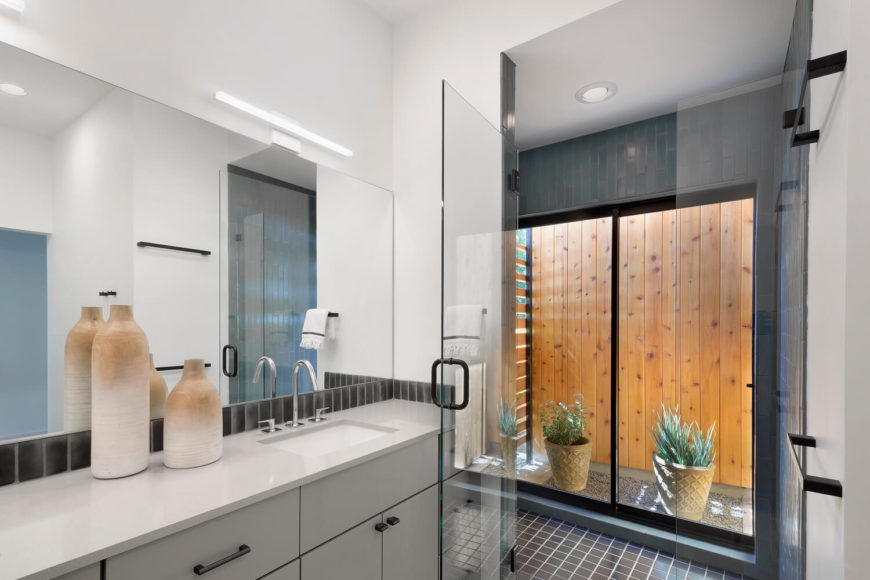 The bathroom features an ultra-modern look, with sleek cabinetry, tile flooring, and glass enclosed shower. A set of sliding glass doors allows direct entry to the courtyard.