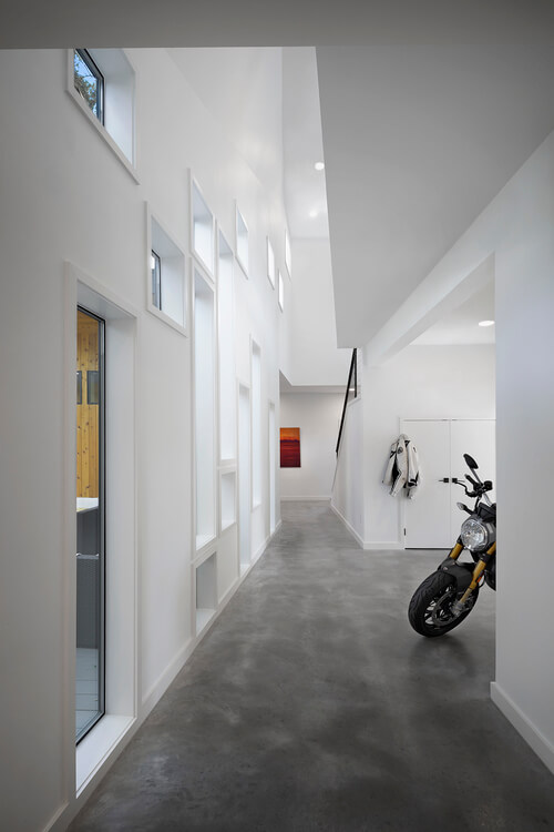 The lengthy hall stands below the open upper floor ceiling, a vast and tall interior space dotted with windows throughout. The foyer boasts storage for both a motorcycle and plenty of outdoor equipment.