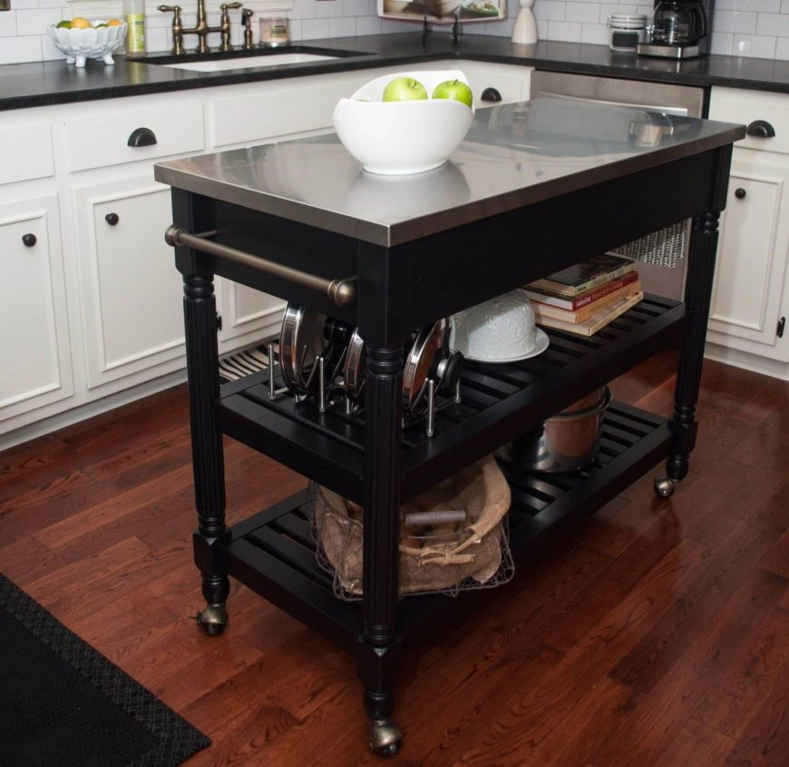 Our final kitchen island design is a unique take on the entire concept, with a slim frame and casters built into the legs for portability. This allows for dynamic placement and extraordinary utility. The black wood frame and stainless steel countertop make for a very sharp, modern appearance in this kitchen with hardwood flooring and white cabinetry.
