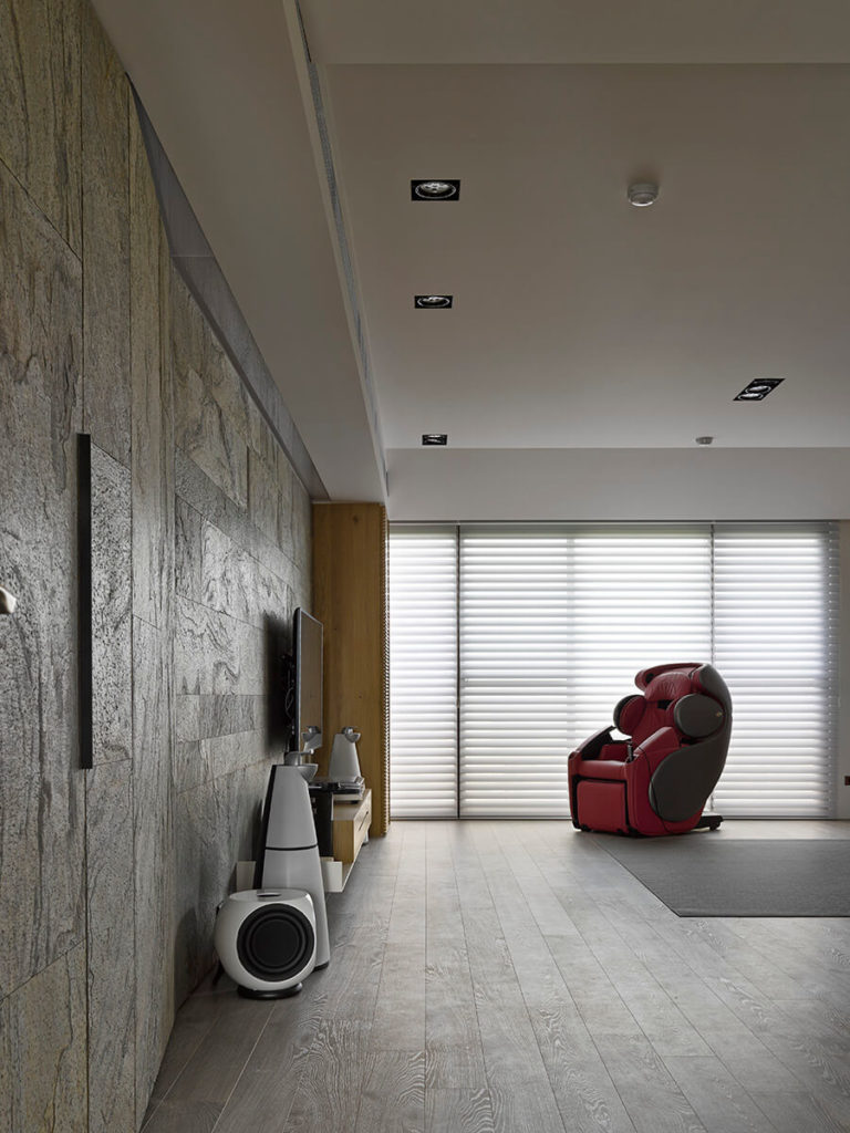 The engaging textures of both the flat stone wall and the dark hardwood flooring adds a nuanced touch to the clean lines and sharp design of the architecture. In front of the large windows, a high tech recliner claims attention.