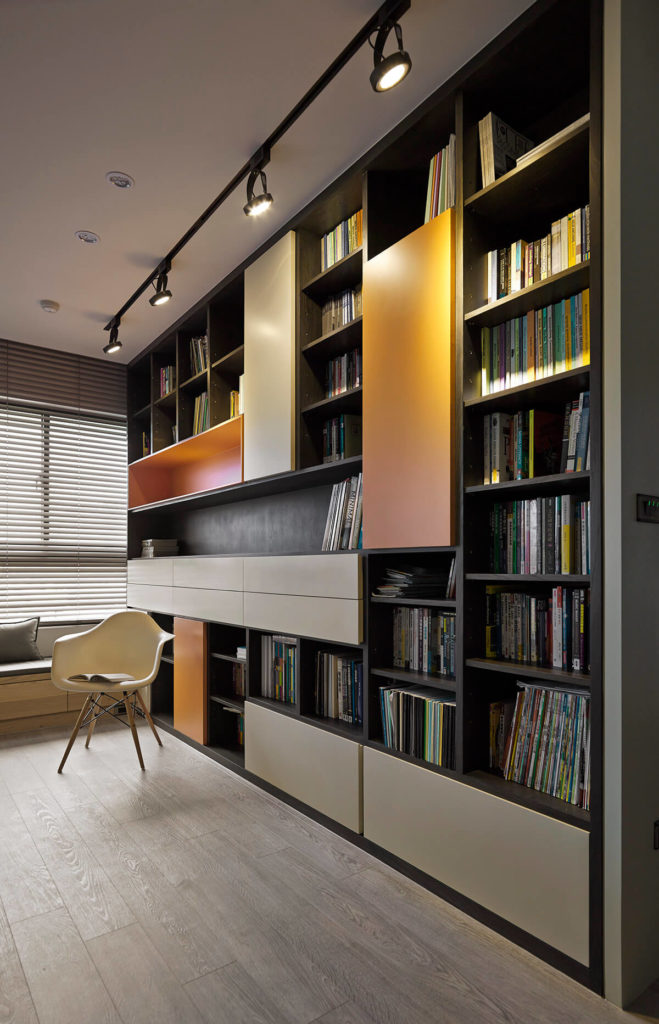 The bookshelf is a true centerpiece item within the grand open space, housing an asymmetrical collection of open shelving and closed cabinets from floor to ceiling. The sleek panels in orange and beige add a crucial modern twist to the classic design.