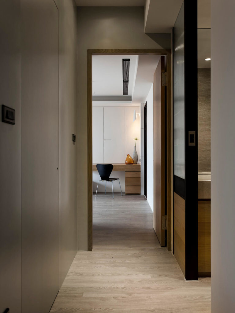 Moving down the hall toward the private areas of the home, we see the muted hardwood flooring continuing unbroken throughout. Splashes of brighter natural wood and sleek white paneling add contrast.