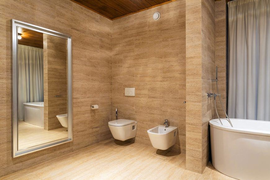 The primary bathroom is fully tiled in a rich, warm beige, and features a small privacy wall separating the soaking tub from the commode. A full-length bathroom mirror is visible to the left.