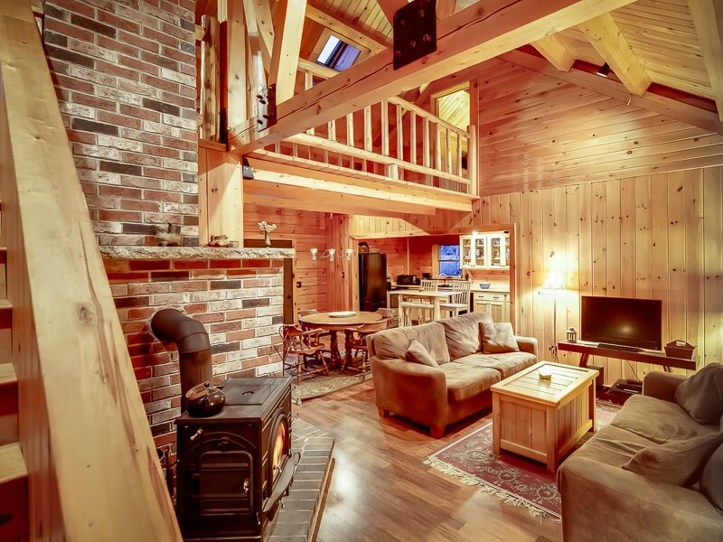 This much more rustic living room features bricks, an old-fashioned wood-burning stove, and extensive use of pine. Around a corner is the equally rustic, but no less luxurious kitchen.