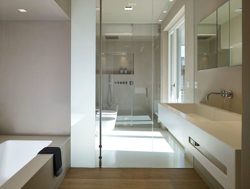 The primary bathroom features a similar design to the downstairs bathroom, with the inclusion of a large soaking tub. The shower and commode are tucked into separate wetrooms, with a door leading out to a terrace.